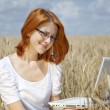 Young Businesswomen in white working with notebook at wheat fiel — Stock Photo #3464964