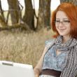 Young fashion girl in glasses and notebook sitting near — Stock Photo #3464998