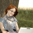 Young fashion girl in glasses and notebook sitting near — Stock Photo #3465040