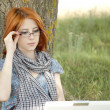 Young fashion girl in glasses and notebook sitting near — Stock Photo #3465055