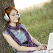 Young smiling fashion girl with notebook and headphones sitting — Stock Photo #3465100