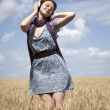 Stock Photo: Young smiling fashion girl with headphones at wheat field.