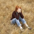 Lonely sad red-haired girl at field — Stock Photo