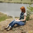 Young beautiful girl with laptop at rock near lake and tree. — Stock Photo