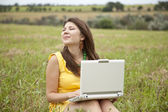 Young beautiful girl with notebook at field — Stock fotografie