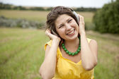 Young smiling fashion girl with headphones at field. — Stock Photo