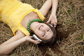 Young beautiful girl in yellow with headphones at field. — Stock Photo