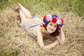 Girl in Slav national wreath lying at field. — Stock Photo