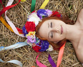 Slav girl with wreath lying at field — Stock Photo