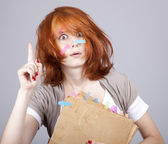 Red-haired student with book and notes on face. — Stock Photo