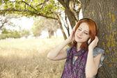 Joven sonriendo moda con auriculares cerca de árbol. — Foto de Stock