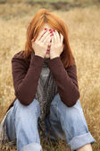 Lonely sad red-haired girl at field — Fotografia Stock