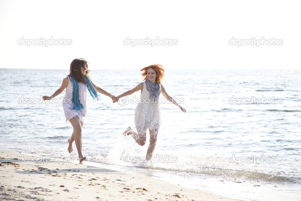 Two beautiful girls running on the beach. — Stock Photo #3463409