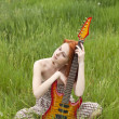 Girl with guitar at field — Stock Photo #3477441