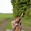 Girl with guitar at village road — Stock Photo #3477443