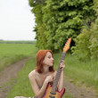 Girl with guitar at village road — Stock Photo #3477444