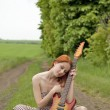 Girl with guitar at village road — Stock Photo #3477446