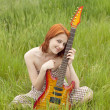 Girl with guitar at field — Stock Photo #3477447