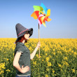 Young sorceress with wind turbine at rape field. — Stock Photo #3477450