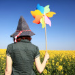 Young sorceress with wind turbine at rape field. — Stock Photo #3477452