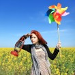 Young girl with wind turbine and retro lamp at rape field. — Stock Photo #3477456