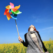 Young girl with wind turbine at rape field. — Stock Photo #3477457