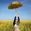 Young woman with umbrella at rape field. — Stock Photo #3477461