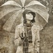 Royalty-Free Stock Photo: Girl with umbrella at park in rainy day. Photo in vintage style