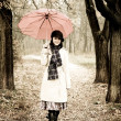 Girl with umbrella at park in rainy day. Photo in vintage style — Stock Photo #3479511