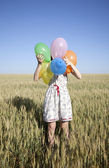 Girl with balloons at wheat field — Stock Photo
