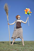Young red-haired witch at green grass field with broom — Stock Photo