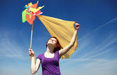 Young girl with wind turbine at rape field. — Stock Photo