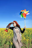 Young girl with wind turbine and retro lamp at rape field. — Stock Photo