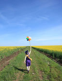Young sorceress with wind turbine at rape field. — Stock Photo