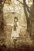 Girl with umbrella at park in rainy day. Photo in vintage style — Stock Photo