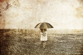 Girl with umbrella at field. Photo in old image style. — Stock Photo