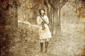 Girl in cloak and scarf with umbrella at park in rainy day. Photo in vintag — Stock Photo