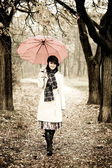 Girl with umbrella at park in rainy day. Photo in vintage style — Photo