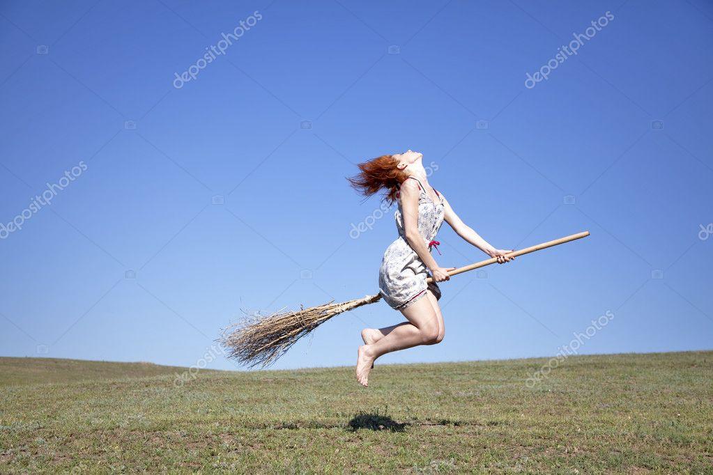 jeune rousse sorcire sur balai volant au dessus de champ dherbe verte image