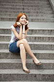 Portrait of beautiful red-haired girl on footstep. — Stock Photo