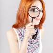 Beautiful red-haired girl with loupe zooming her eye — Stock Photo