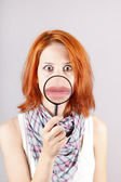 Beautiful red-haired girl with loupe zooming her mouth. — Stock Photo