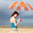 Girl with umbrella at field — Stock Photo #3569240