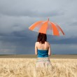 Girl with umbrella at field in rainy day. — Stock Photo