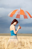 Girl with umbrella at field — Stock Photo