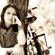 Beautiful girl sitting near bike and tree at rest in forest. Photo in retro - Стоковая фотография