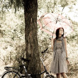 Beautiful girl near bike and tree at rest in forest. Photo in retro — Stock Photo