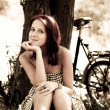 Beautiful girl sitting near bike and tree at rest in forest. Photo in retro - Foto Stock