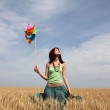 Girl with wind turbine at wheat field — Stock Photo