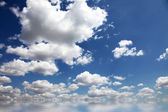 Blue sky and clouds over abstract water. — Stock Photo